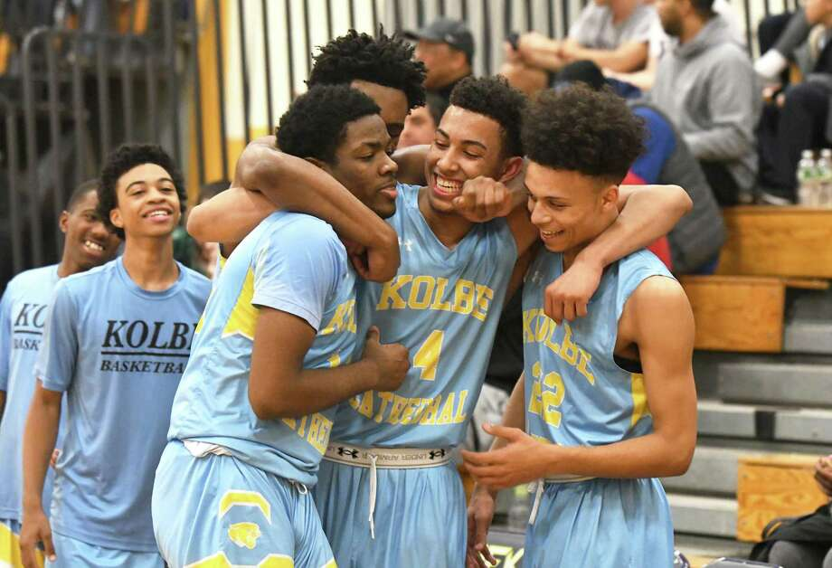 Kolbe players including, from left, Anthony Senior, Quinton Sneed, Kyle Federici (4), and Demetrius Gordon celebrate their win after the Division IV boys basketball semifinal between Kolbe Cathedral and Northwestern at Kennedy High in Waterbury, March 14, 2018. Photo: Krista Benson / For Hearst Connecticut Media / The News-Times Freelance
