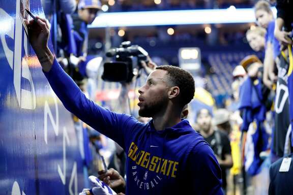 Golden State Warriors' Stephen Curry signs an autograph before Warriors' game against Los Angeles Lakers at Oracle Arena in Oakland, Calif., on Wednesday, March 14, 2018.