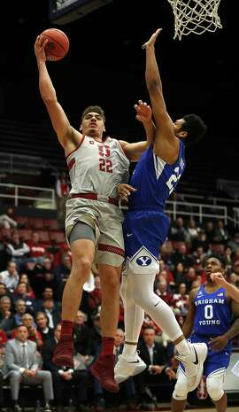 Stanford forward Reid Travis (22) drives to the basket against BYU forward Yoeli Childs (23) during the first half of an NCAA college basketball game in the first round of the NIT on Wednesday, March 14, 2018, in Stanford, Calif. (AP Photo/ Tony Avelar)