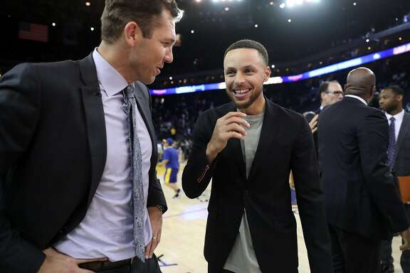 Golden State Warriors' Stephen Curry chats with Los Angeles Lakers' head coach Luke Walton after Warriors' 117-106 win in NBA game at Oracle Arena in Oakland, Calif., on Wednesday, March 14, 2018.