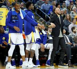 Golden State Warriors' Andre Iguodala and Stephen Curry enjoy watching 4th quarter action as Warriors defeat Los Angeles Lakers 117-106 in NBA game at Oracle Arena in Oakland, Calif., on Wednesday, March 14, 2018.