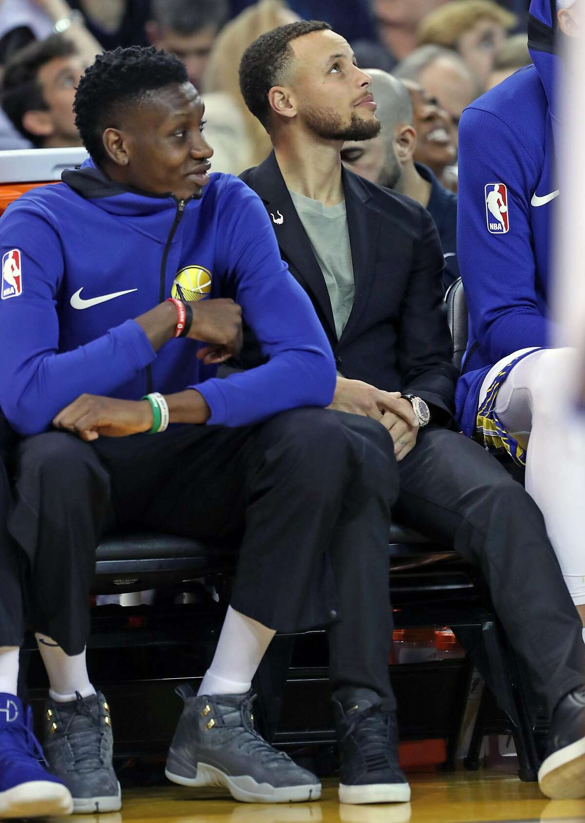 Golden State Warriors' Stephen Curry and Chris Boucher watch action in 2nd quarter against Los Angeles Lakers during NBA game at Oracle Arena in Oakland on Wednesday, March 14, 2018.