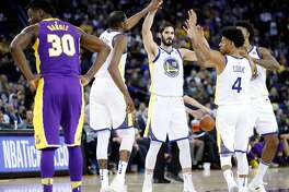 Golden State Warriors' Kevin Durant, Omri Casspi, Quinn Cook and Nick Young high five after Los Angeles Lakers' Julius Randle fouled in 4th quarter during Warriors' 117-106 win in NBA game at Oracle Arena in Oakland, Calif., on Wednesday, March 14, 2018.