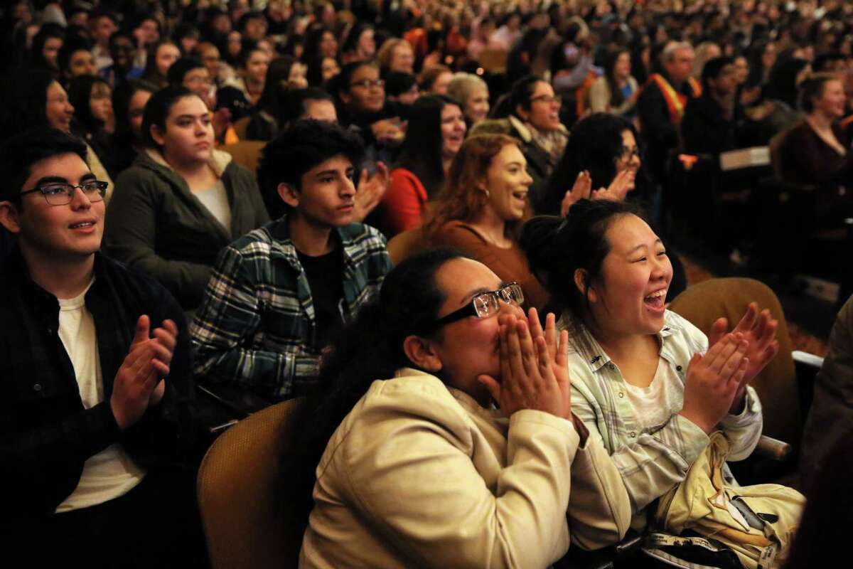 Bridget Camarillo, bottom left, and Angel Chang, of Highline High School, cheer as they and students from 35 Washington and Oregon high schools attend a performance of