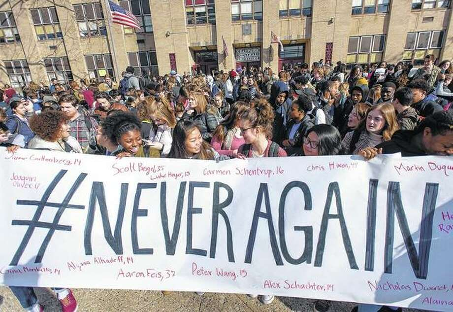 Students from Champaign Central High School hold a banner with the names of the victims from the Marjory Stoneman Douglas High School shooting as they gather outside of the school during a student walkout Wednesday in Champaign. Students around the area and across the country participated in walkouts Wednesday to protest gun violence, one month after the deadly shooting inside a high school in Parkland, Florida.