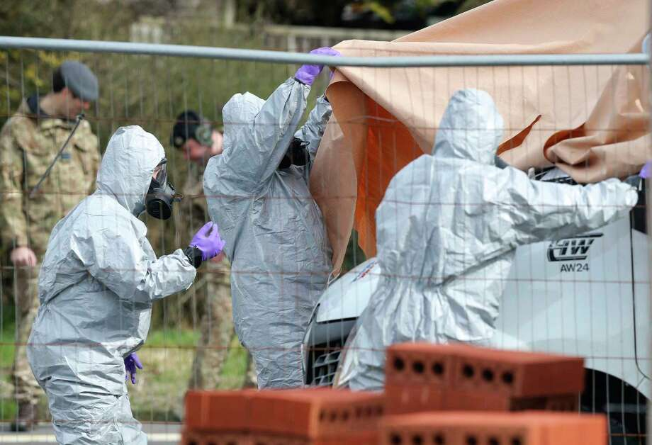 Soldiers wearing protective clothing cover  a tow truck in Hyde Road, Gillingham, Dorset, England as the investigation into the suspected nerve agent attack on Russian double agent Sergei Skripal continues Wednesday March 14, 2018.  The army cordoned off a road in Dorset on Wednesday as the investigated the attack on Sergei Skripal and his daughter Yulia. Authorities have cordoned off several sites in and near Salisbury, 90 miles (145 kilometers) southwest of London as part of their probe.  (Andrew Matthews/PA via AP) Photo: Andrew Matthews / PA