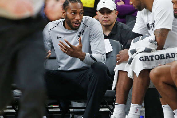 SAN ANTONIO,TX - MARCH 13 :  Kawhi Leonard #2 of the San Antonio Spurs still not playing talks with teammate LaMarcus Aldridge #12 of the San Antonio Spurs during game against the Orlando Magic at AT&T Center on March 13, 2018  in San Antonio, Texas.  NOTE TO USER: User expressly acknowledges and agrees that , by downloading and or using this photograph, User is consenting to the terms and conditions of the Getty Images License Agreement. (Photo by Ronald Cortes/Getty Images)