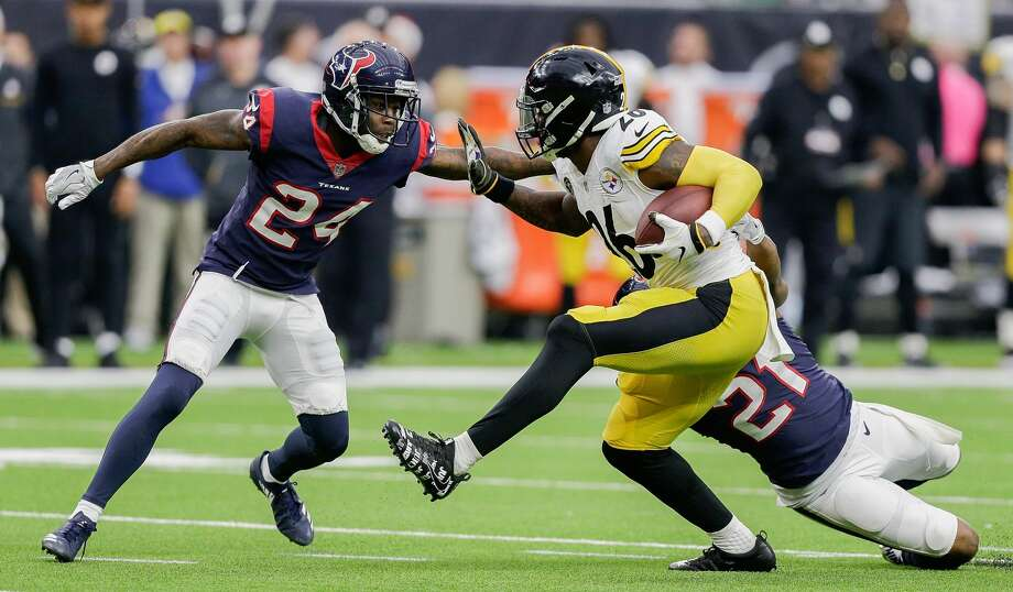 HOUSTON, TX - DECEMBER 25:   Le'Veon Bell #26 of the Pittsburgh Steelers rushes with the ball as Marcus Gilchrist #21 of the Houston Texans and Johnathan Joseph #24 look to make a tackle during game action at NRG Stadium on December 25, 2017 in Houston, Texas. The Pittsburgh Steelers defeated the Houston Texans 34-6. (Photo by Bob Levey/Getty Images) Photo: Bob Levey/Getty Images