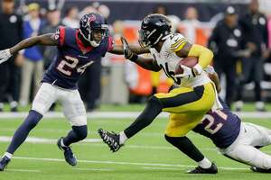 HOUSTON, TX - DECEMBER 25:   Le'Veon Bell #26 of the Pittsburgh Steelers rushes with the ball as Marcus Gilchrist #21 of the Houston Texans and Johnathan Joseph #24 look to make a tackle during game action at NRG Stadium on December 25, 2017 in Houston, Texas. The Pittsburgh Steelers defeated the Houston Texans 34-6. (Photo by Bob Levey/Getty Images)