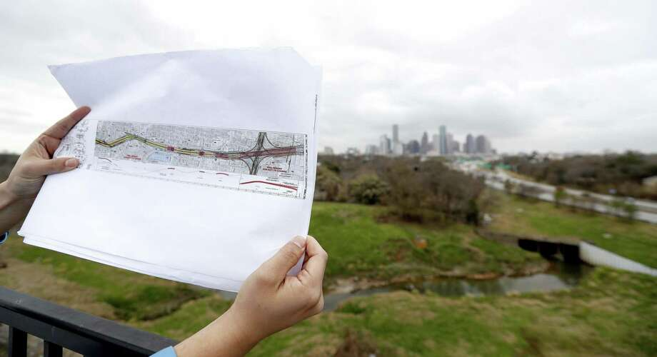 Jorge Bustamante with the Greater Northside Management District holds up a map while standing in The Raven's Tower, overlooking the Near Northside area potentially impacted by widening Interstate 45. Photo: Karen Warren / Karen Warren / Houston Chronicle / © 2018 Houston Chronicle
