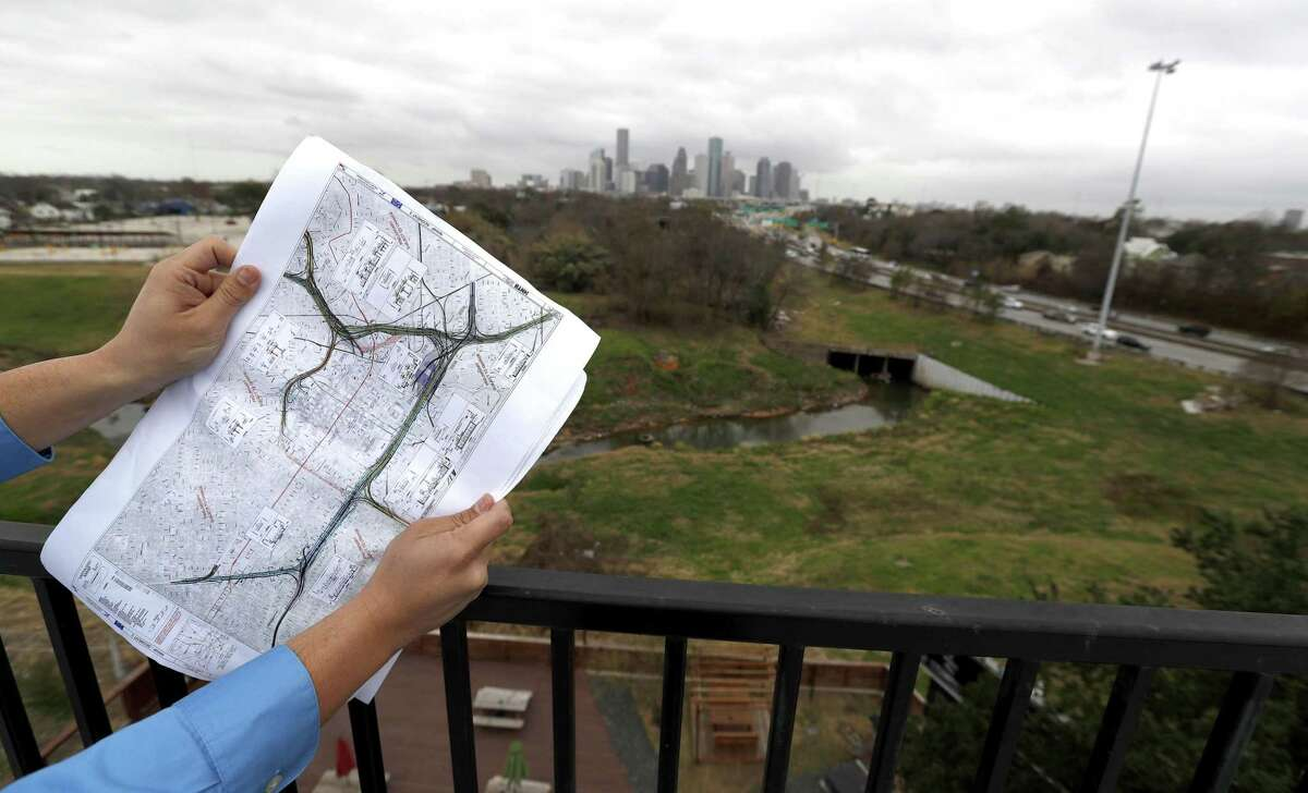 Jorge Bustamante with the Greater Northside Management District holds up a map while standing in The Raven's Tower, overlooking the Near Northside area potentially impacted by widening Interstate 45.