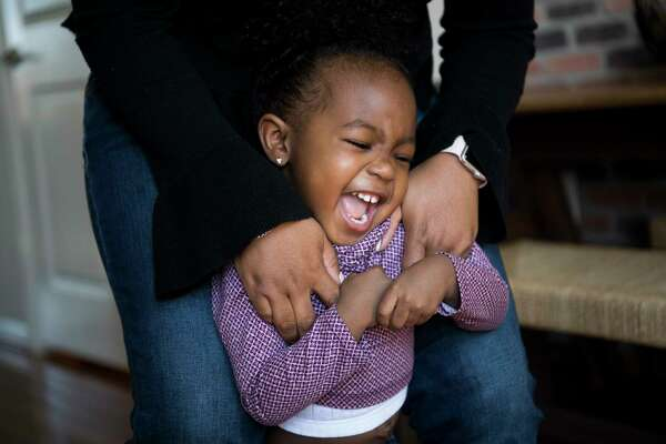 Parker Curry gets tickled by her mother, Jessica Curry, at home in Washington, D.C. After a photograph of Parker admiring Michelle Obama's portrait at the National Portrait Gallery went viral, life got out of hand.
