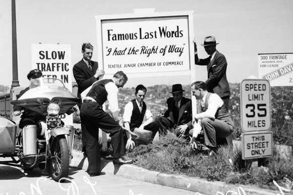 "Traffic safety sign at Aurora Bridge, Seattle, 1936. In this photo, men install a traffic safety sign at the entrance of the George Washington Memorial Bridge, often called the Aurora Bridge, on U. S. Highway 99. The large sign reads: Famous Last Words ""I had the right of way"", Seattle Junior Chamber of Commerce. The Junior Chamber of Commerce was established in 1931 with a mission of community service, training and networking for young people. It is known today as the Seattle Jaycees."