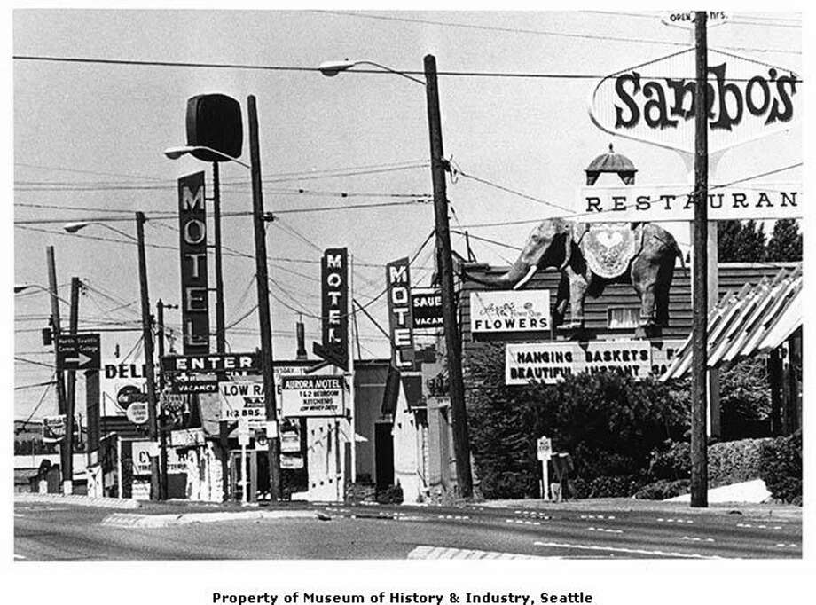 "Sambo's sign on Aurora Avenue, Seattle, July 29, 1976.  The first Sambo's restaurant opened in Santa Barbara, California, in 1957 as a low-priced pancake house catering directly to blue-collar customers. The name came to be a racist slur for a loyal and contented black servant. This image was taken facing north on Aurora Avenue North. Also visible in this image is the ""Aurora elephant,"" a roadside fixture since the 1930s. The elephant was renovated in 2009 and still stands in the same location over a tool rental shop as of 2018. Photo: PI File"