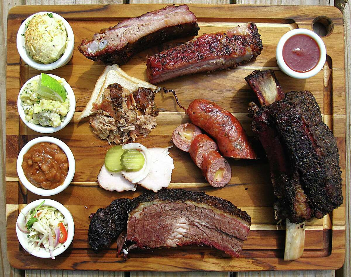 Barbecue and sides from Texas 46 BBQ in Spring Branch. Clockwise from top left: potato salad, pork ribs, barbecue sauce, beef rib, brisket, cole slaw, cowboy beans, creamed corn, pulled pork, jalapeño-cheese sausage and turkey.
