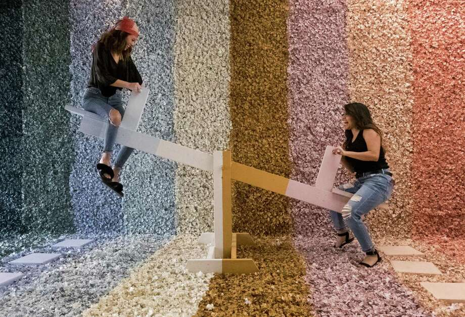 Friends Abby Marin (right) and Sarah Garcia play on the see-saw in the Flower Vault's Rainbow Room. The shop has five distinct rooms for taking photos intended for social media. Photo: Kin Man Hui /San Antonio Express-News / ©2018 San Antonio Express-News