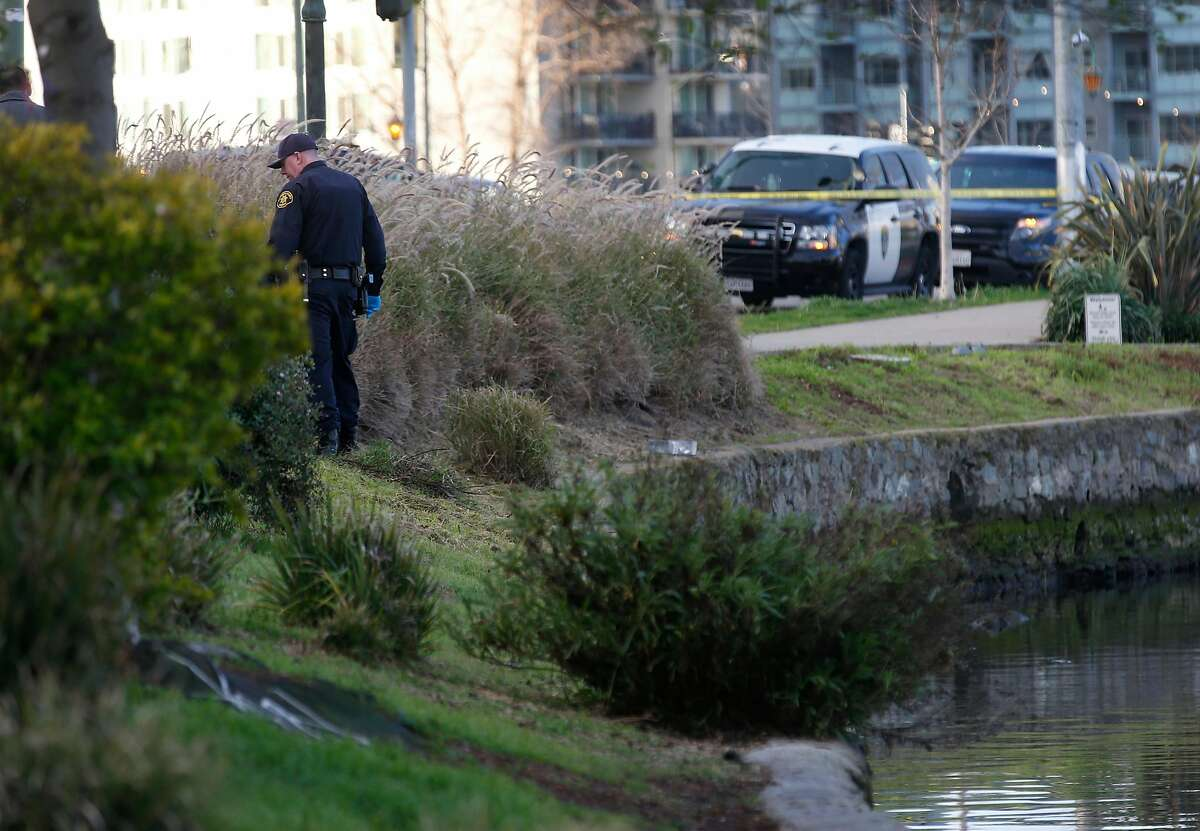 A police officer searches the shoreline of Lake Merritt after two people fell into the water and drowned before dawn in Oakland on Thursday.