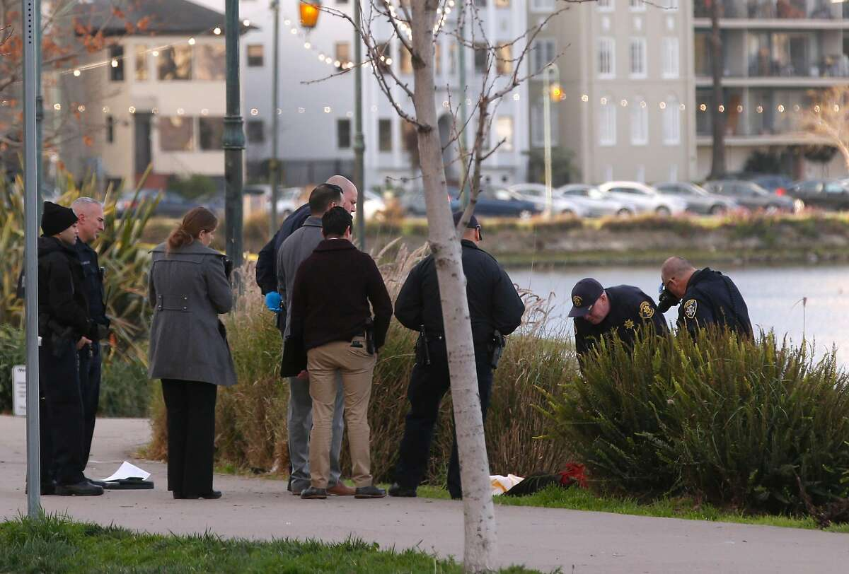Police officials investigate along the shoreline of Lake Merritt in Oakland after two people drowned early Thursday. A man died in the hospital and a woman's body was recovered by Fire Department divers. Witnesses reported hearing an altercation before the drowning.