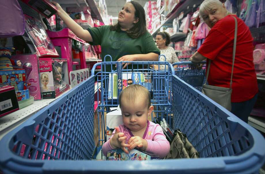 In this Nov. 28, 2008, file photo, Jessica Luu, left, looks for deals as her friend's baby, Kaylee Oliver, inspects a toy in the shopping cart, as shoppers at Toys R Us at The Forum at Olympia Parkway in Selma, Texas. Toys R Us CEO David Brandon told employees Wednesday, March 14, 2018, that the company's plan is to liquidate all of its U.S. stores, according to an audio recording of the meeting obtained by The Associated Press. Photo: Bob Owen /San Antonio Express-News / AP2008