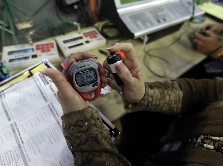 Rodeo timers Mary Brunner holds her stop watch and plunger that start and stop the timers near the dirt on the 50-yard line at the Houston Livestock Show and Rodeo at NRG Stadium, Tuesday, March 13, 2018, in Houston. The stop watch is a backup for the plunger.  ( Karen Warren / Houston Chronicle ) Photo: Karen Warren, Staff / Houston Chronicle / © 2018 Houston Chronicle