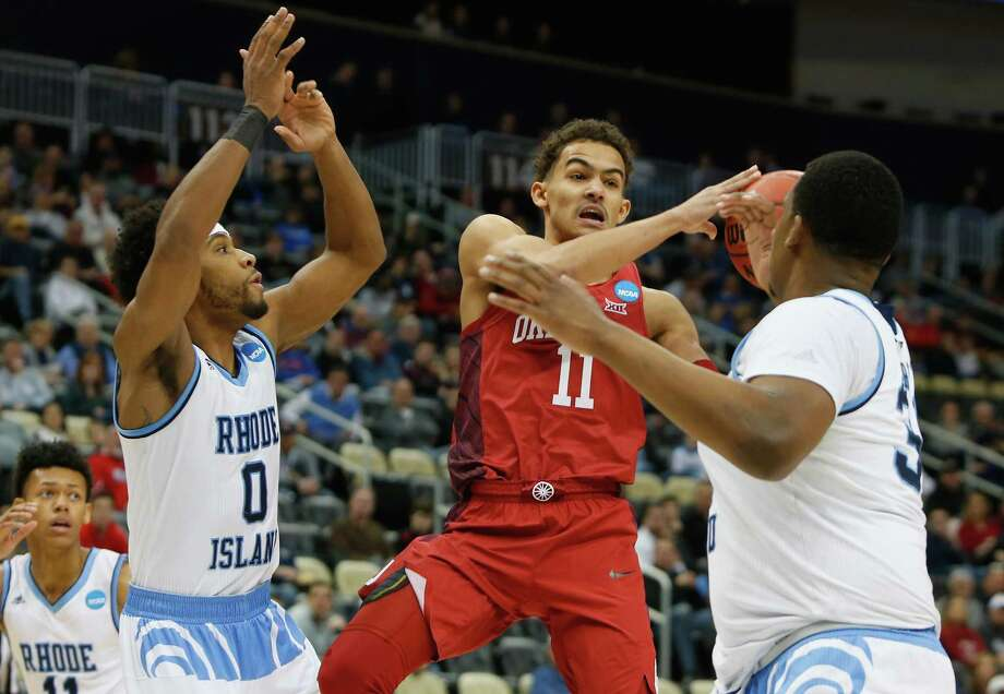 PITTSBURGH, PA - MARCH 15:  Trae Young #11 of the Oklahoma Sooners is defended by E.C. Matthews #0 and Andre Berry #34 of the Rhode Island Rams in the first half of the game during the first round of the 2018 NCAA Men's Basketball Tournament at PPG PAINTS Arena on March 15, 2018 in Pittsburgh, Pennsylvania. Photo: Justin K. Aller, Getty Images / 2018 Getty Images