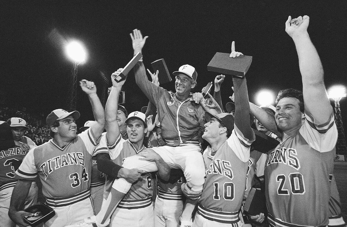 FILE - In this June 10, 1984, file photo, Cal State Fullerton Coach Augie Garrido, center, is lifted by his 1984 NCAA Baseball Championship Team as they celebrate after a 3-1 victory over Texas in the College World Series final baseball game in Omaha, Neb. Garrido, who won three national baseball championships at Cal State Fullerton and two more at Texas, has died, the University of Texas announced Thursday, March 15, 2018. He was 79. (AP Photo/File)