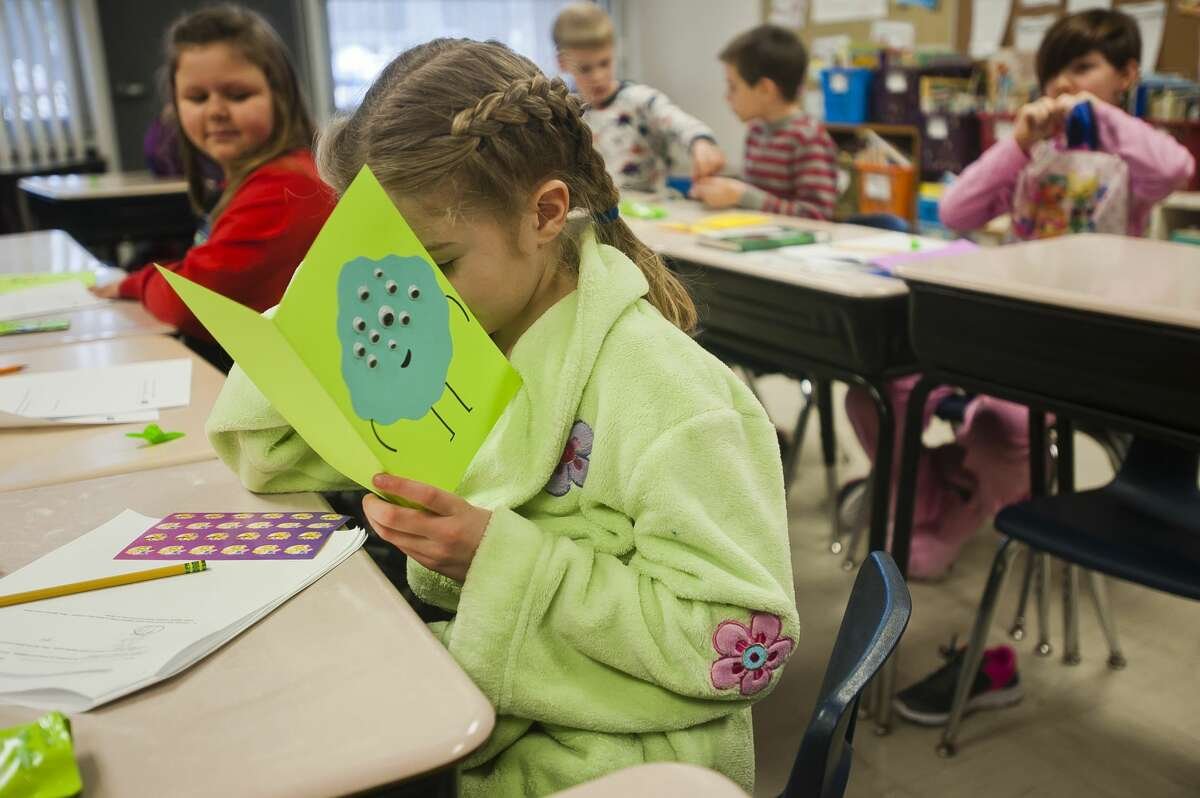 Gracelyn Furlo, 8, checks out a card containing a sheet of stickers she received as a gift from Bullock Creek High School students on Thursday, March 15, 2018 at Floyd Elementary. The high school students are part of a group called Creekers for a Cause, of which Brown is the advisor, and chose to visit classrooms in honor of