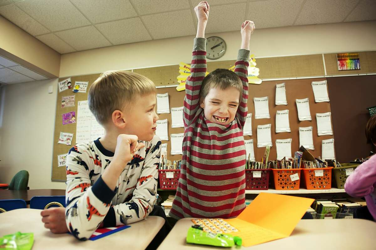Drake Desmarteaux, 8, thrusts his hands into the air after receiving a snack and a card containing a sheet of stickers as a gift from Bullock Creek High School students on Thursday, March 15, 2018 at Floyd Elementary. The high school students are part of a group called Creekers for a Cause and chose to visit classrooms in honor of
