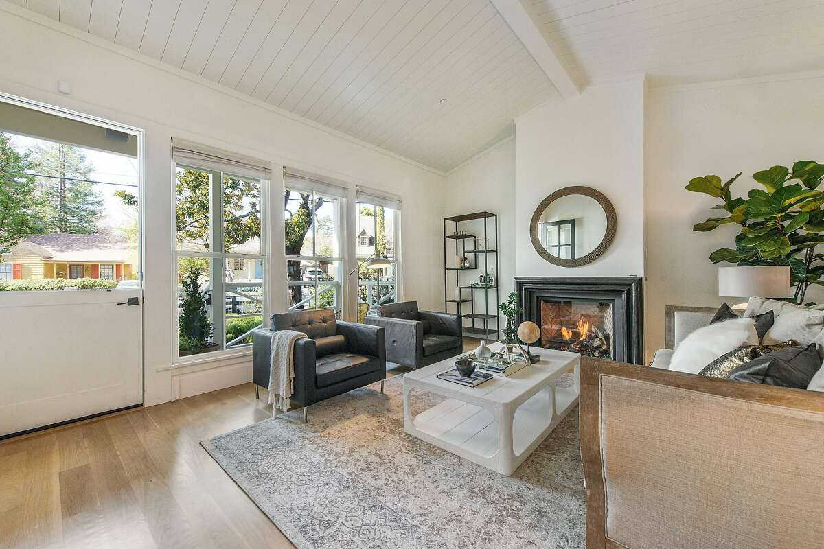 The living room features a Dutch door, large windows and a vaulted, beamed ceiling.�