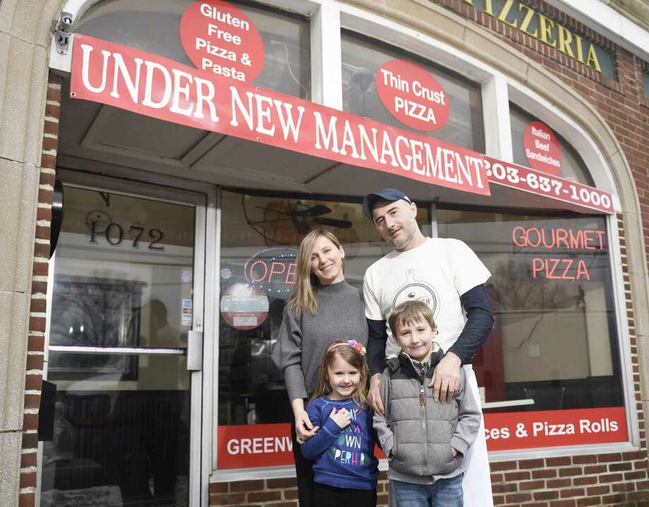 Co-owners Jon and Leonita Marleku pose with their children Eva, 4, and Dion, 7, at Greenwich Pizzeria, now under new management, in the Riverside section of Greenwich, Conn. Tuesday, March 13, 2018. Photo: Tyler Sizemore / Hearst Connecticut Media / Greenwich Time