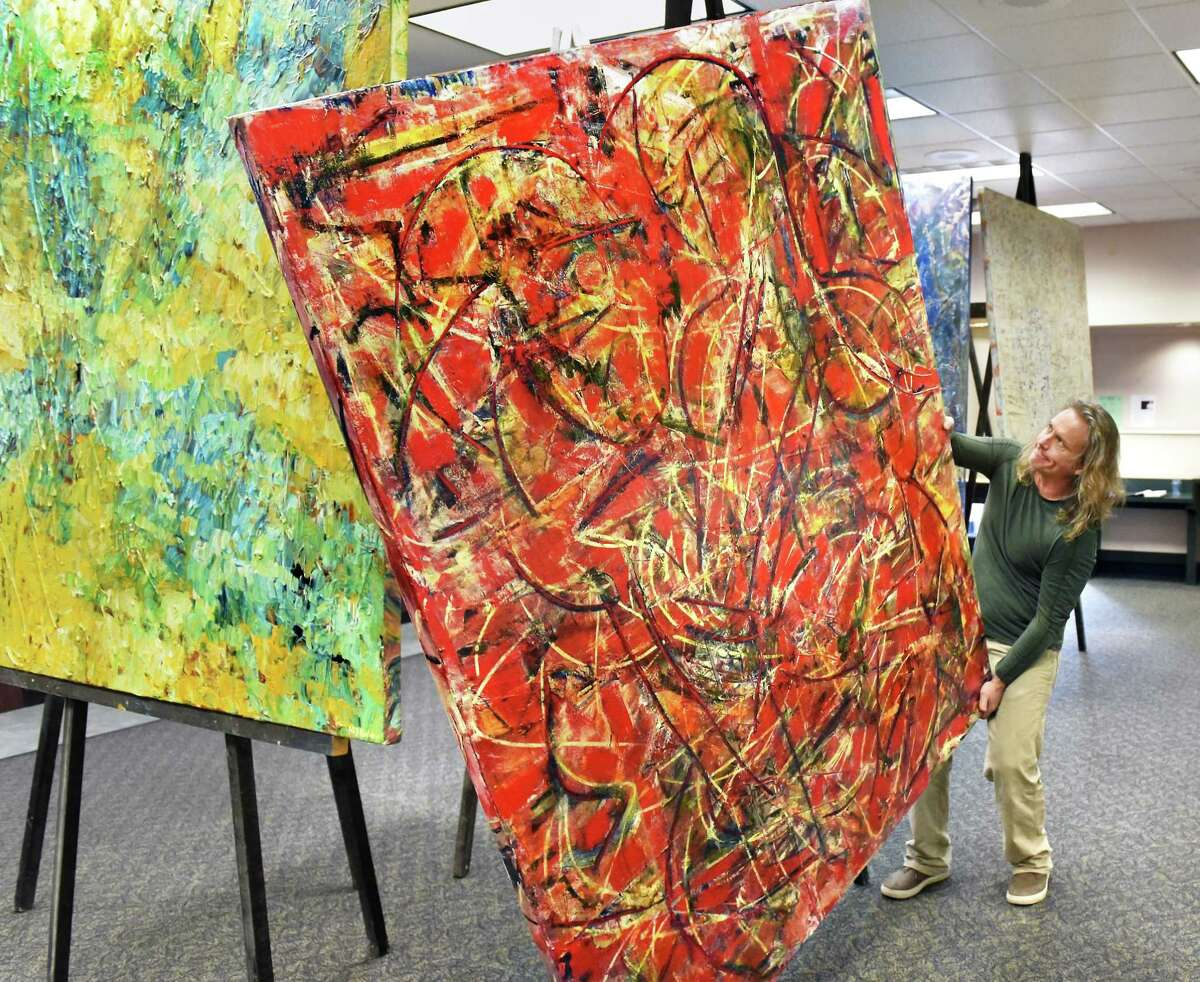 Artist Michael Nighswonger rolls one of his 45 contemporary abstract acrylic on canvas works into position for a 10-day pop-up exhibit inside the old bank Thursday March 15, 2018 in Delmar, NY. (John Carl D'Annibale/Times Union)