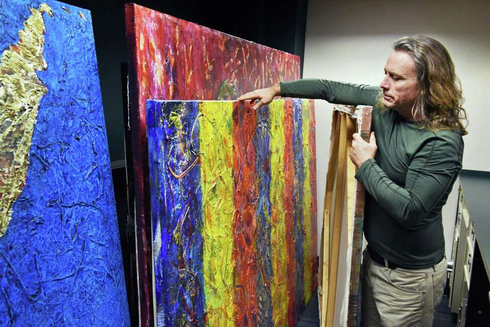 Artist Michael Nighswonger prepares some of his 45 contemporary abstract acrylic on canvas works for a 10-day pop-up exhibit inside the old bank Thursday March 15, 2018 in Delmar, NY. (John Carl D'Annibale/Times Union)