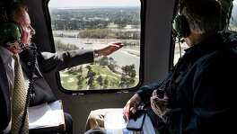 Dave Martin, Houston city councilman, District E, left, speaks to Gov. Greg Abbott as they take an aerial tour over theSanJacintoRiver, downstream from Lake Conroe, on Thursday, March 15, 2018, in Houston. The Kingwood area suffered serious flooding during Hurricane Harvey due in part to sand washed downstream from sand mining operations along the river.
