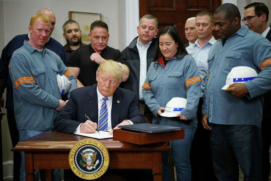 Surrounded by a group of steel workers, President Trump signs off on trade tariffs for steel and aluminum. A reader wonders if the tariffs are a good idea. Photo: MANDEL NGAN /AFP /Getty Images / AFP