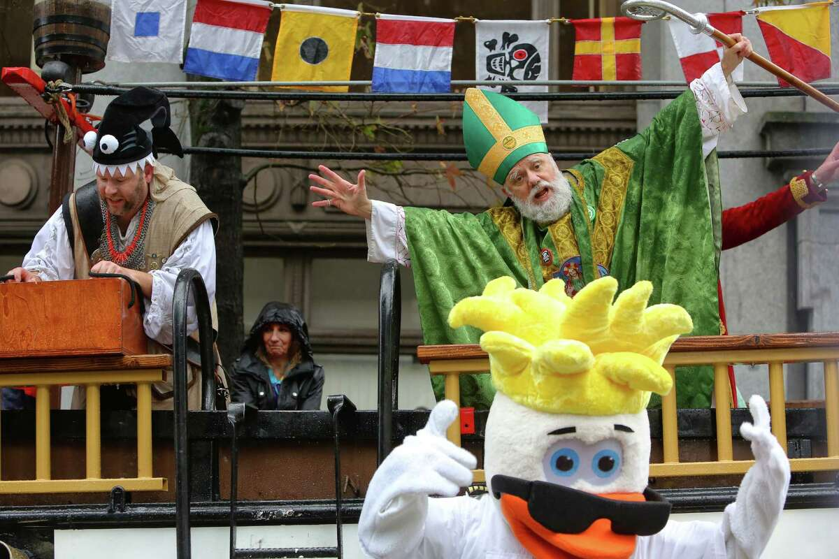 Saint Patrick and the Ride the Ducks mascot dance during the annual St. Patrick's Day parade in downtown Seattle, Saturday, March 11, 2017. (Genna Martin, seattlepi.com)
