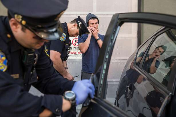 Mission District San Francisco Police Officers Robert Clendenen, left, attempts to lift fingerprints while Officer Paul Lujano, center, interviews  Michael Lech after his car was broken into near Potrero Street and 24th Avenue Thursday, Feb. 1, 2018 in San Francisco, Calif.