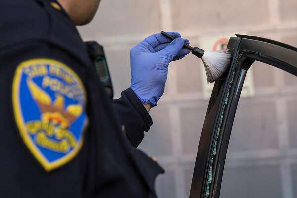 Mission District San Francisco Police Officer Robert Clendenen attempts to lift fingerprints while investigating an auto burglary near Potrero Street and 24th Avenue Thursday, Feb. 1, 2018 in San Francisco, Calif.