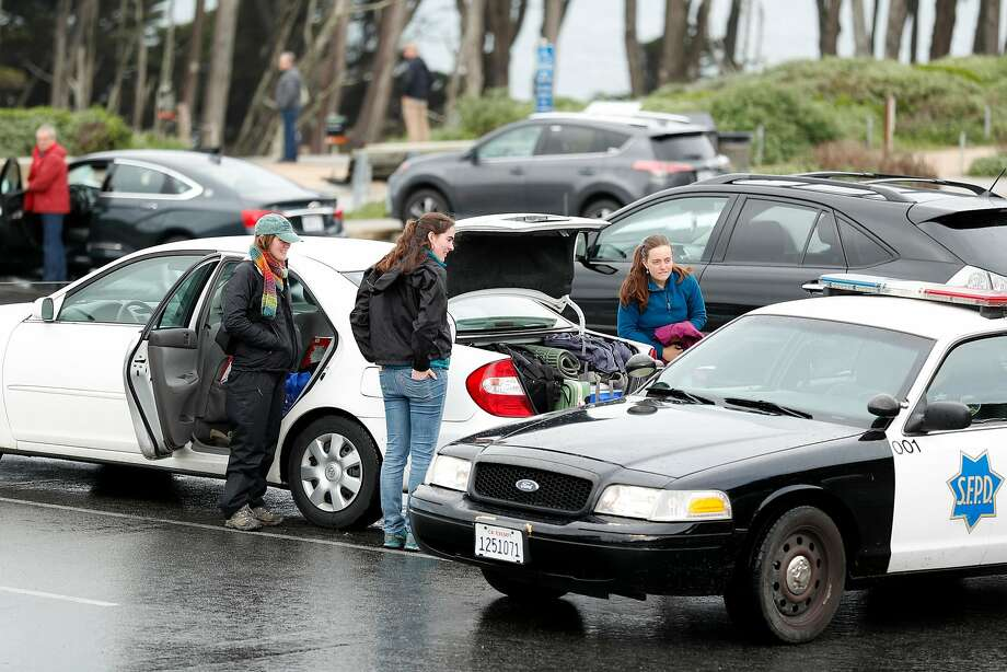An officer warns women not to leave valuables in their car near Lands End. Photo: Scott Strazzante, The Chronicle