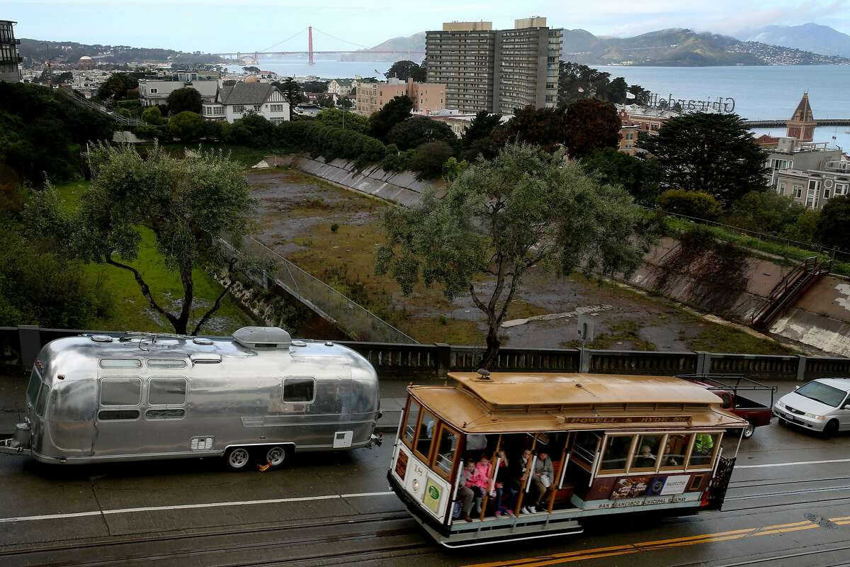 A cable car rides along Hyde Street next to the Francisco Reservoir, Tuesday, March 13, 2018, in San Francisco, Calif. The site is located in the Russian Hill neighborhood at Francisco Street and Hyde Street.
