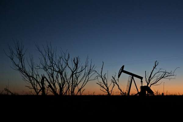 The silhouette of a pumpjack is seen at dusk in the Permian Basin near Midland, Texas, U.S., on Friday, March 2, 2018. Chevron, the world's third-largest publicly traded oil producer, is spending $3.3 billion this year in the Permian and an additional $1 billion in other shale basins. Its expansion will further bolster U.S. oil output, which already exceeds 10 million barrels a day, surpassing the record set in 1970. Photographer: Daniel Acker/Bloomberg