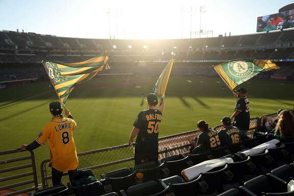 Oakland Athletics' fans in left field bleachers wave flags at Oakland Coliseum in Oakland, Calif. on Monday, July 17, 2017.