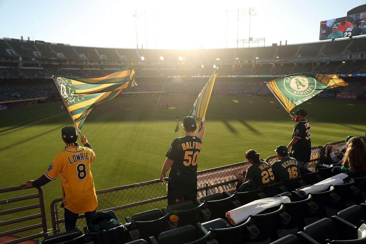 Oakland Athletics' fans wave flags at Oakland Coliseum.