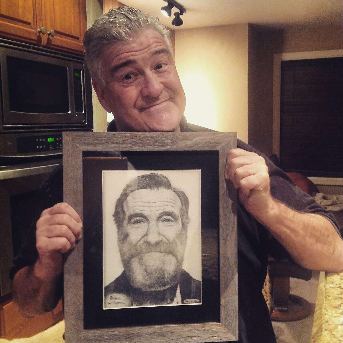 Michael Pritchard holds a framed drawing of the late comic Robin Williams. It was a gift to Pritchard from the artist, a brain-injured veteran in the Pathway Home program at the Veterans Home of California in Yountville (Napa County). Courtesy photo.