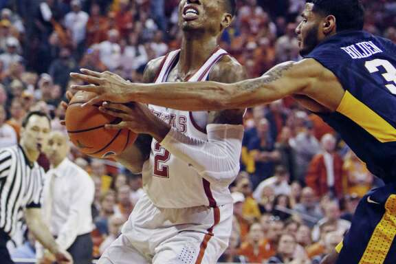 Texas guard Kerwin Roach, Jr., left, drives the ball against West Virginia guard James Bolden, right, during the second half of an NCAA college basketball game, Saturday, March 3, 2018, in Austin, Texas. Texas won 87-79. (AP Photo/Michael Thomas)