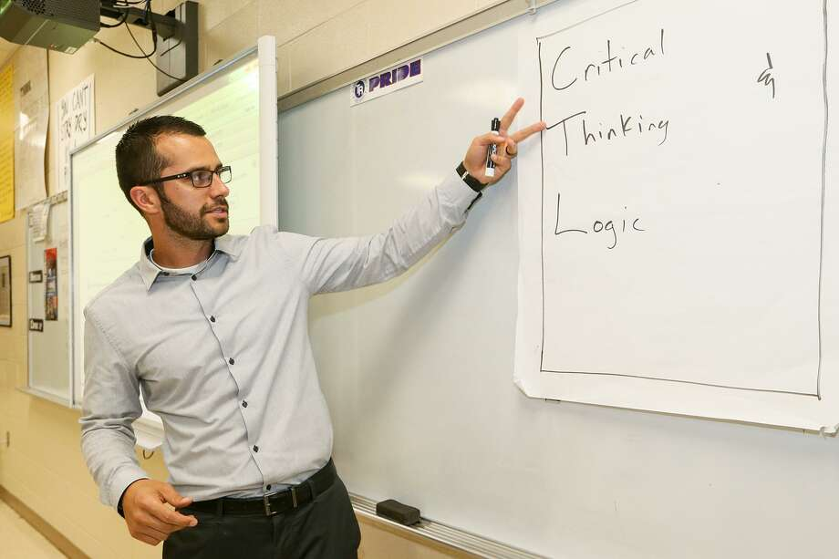 "Ali Goljahmofrad points to the sign he put up on the first day of class in his advanced quantitative reasong class at Roosevelt High School on April 17, 2017. The sign originally just had the letters ""C, L, and T"" and he expanded that to ""Critical Thinking and Logic with the class. Goljahmofrad was one of two local teachers to receive the 2017 Trinity Prize for Excellence in Teaching, the greater San Antonio's oldest and most prestigious teaching award. Photo: Marvin Pfeiffer, Staff / San Antonio Express-News / Express-News 2017"