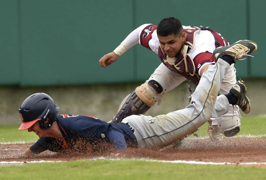 Marshall catcher Nico Lopez applies a late tag as Ben Surrett of Brandeis scores in top of the first inning  in District 28-6A action at the Northside athletic complex on Thursday, March 15, 2018. Photo: Billy Calzada, Staff / San Antonio Express-News / San Antonio Express-News