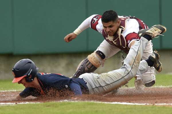 Marshall catcher Nico Lopez applies a late tag as Ben Surrett of Brandeis scores in top of the first inning  in District 28-6A action at the Northside athletic complex on Thursday, March 15, 2018.
