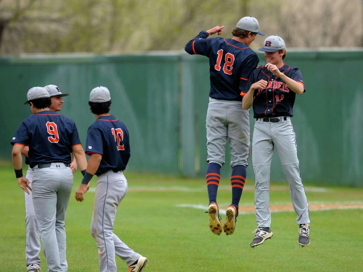 Chris Kollman of Brandeis, right, celebrates with pitcher Ty Fontenot (18) after the team's 14-1 victory over Marshall in District 28-6A action at the Northside athletic complex on Thursday, March 15, 2018.