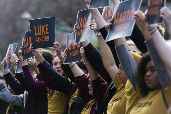 Demonstrators hold up placards with the names of the shooting victims from Marjory Stoneman Douglas High School in Parkland, Fla., during a student walkout to protest gun violence, Wednesday, March 14, 2018,  in front of the NRA offices at the Capital Mall in Sacramento, Calif. (Paul Kitagaki Jr./The Sacramento Bee via AP)