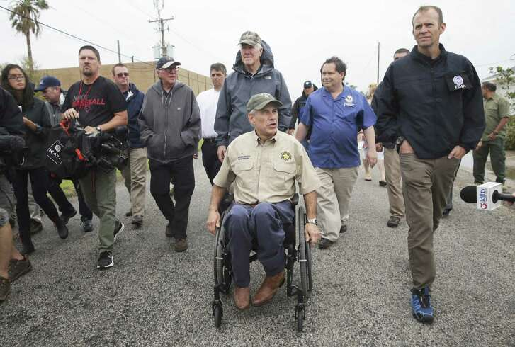Governor Greg Abbott walks with Senator John Cornyn and FEMA representative Brock Long as he visits Rockport on August 28, 2017.